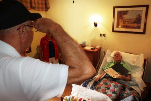 Veteran volunteer honoring hospice patient's military service with a salute, certificate and pin